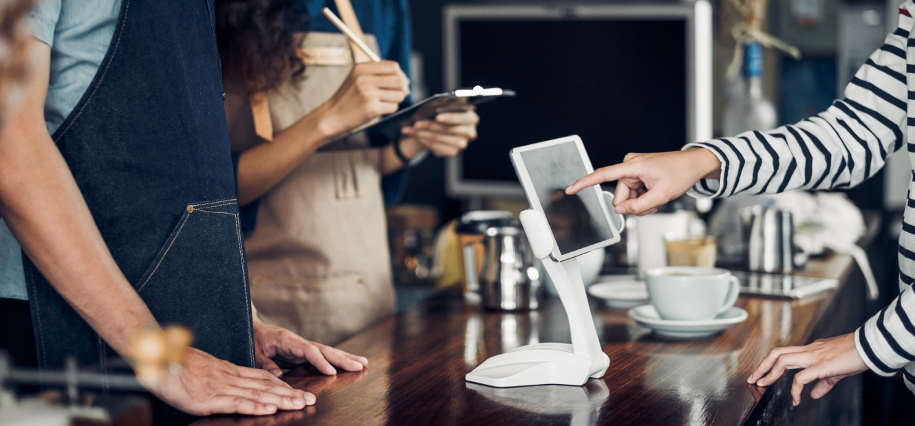 Person ordering coffee and paying on tablet payment system