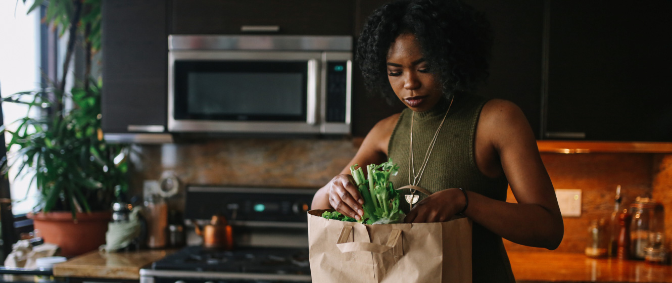 Woman unloading groceries in her kitchen